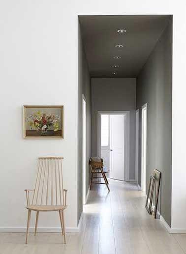 Parquet clair et peinture gris perle décore ce couloir sombre. Un style chic et élégant accentué par les encadrements de portes peints en blanc et le parquet