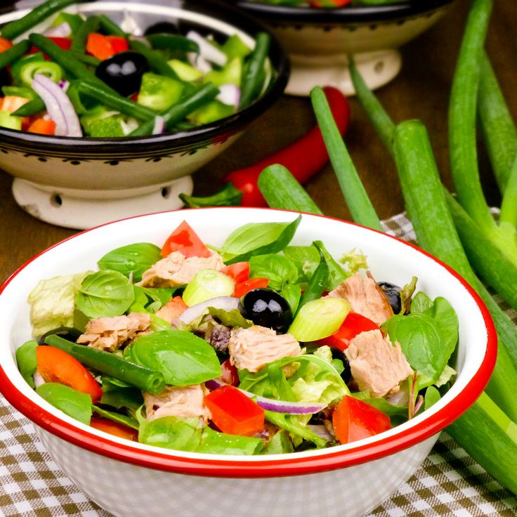 Zomerse maaltijdsalade met tonijn, beetgaar gekookte haricots verts, verse basilicum, zwarte olijven, rode paprika, bosui en gemengde sla. Heerlijk met knoflooktoast. Serveer dit gerecht ook eens als een gezond voorgerecht.