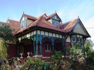 Federation style - australian style architecture homes. The terracotta roof tiling was a common material and look utilised in this era. The dark green wooden balcony features along with cream colours and brick was a popular scheme to follow