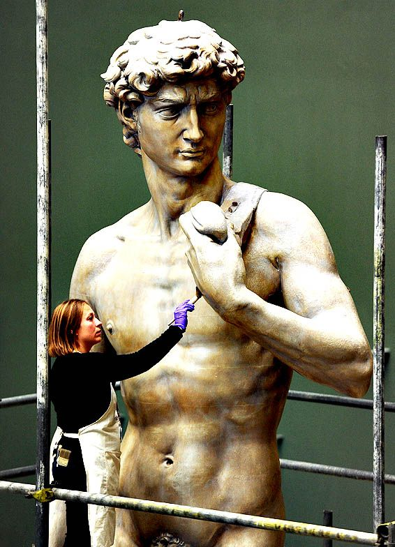 Johanna Puisto, a sculpture conservator at the Victoria & Albert Museum, unveils a cast of Michelangelo's David on Monday in London, England. Stuart C. Wilson (Getty Images)