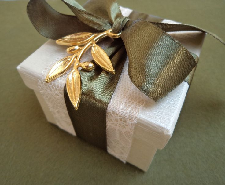 Off white favour box decorated with lace, olive green satin ribbon and a gold metallic olive leaf.