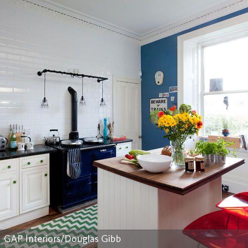 Die unkonventionelle, farbenfrohe Küche vereint selbstbewusst verschiedene Stile, Materialien und Farben, ohne unruhig zu wirken. Der traditionelle Herd ist…