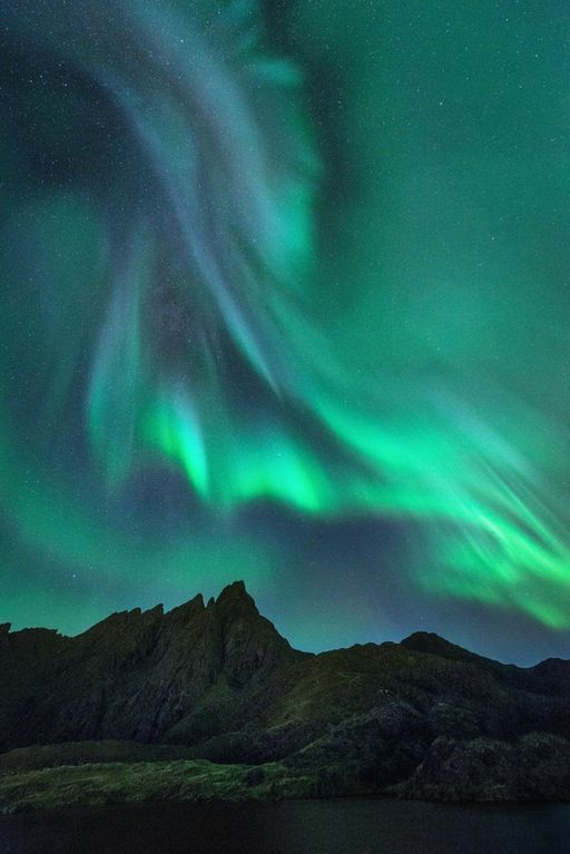 "Aurora ""corona"" over jagged peaks near Leknes, Norway [OC][1,335x2,000] : EarthPorn"