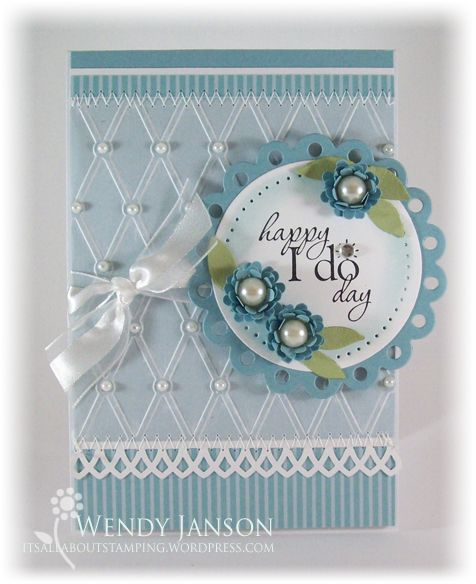 Stamps:  Word Play,  Paper:  Whisper White, Baja Breeze & DSP, Vellum  Ink:  Stazon Jet Black, Baja Breeze  Accessories:  Sponge dauber, Organza ribbon, rhinestone, pearls, Mat Pack, Little Leaves Sizzlit, Spring Bouquet flower punch (retired), MS border punch, Nesties, Embossing Folder