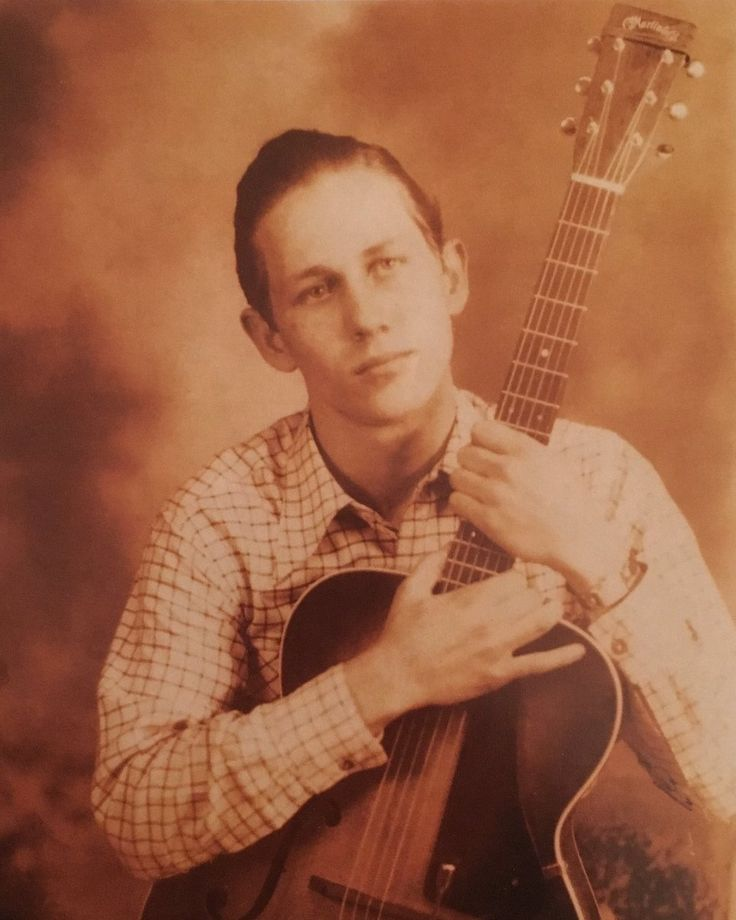 Chet Atkins in 1943 cradling an archtop Martin Guitar.
