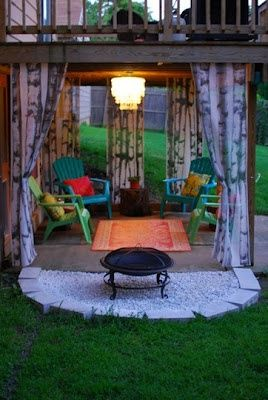 under deck patio -- love the lighting, curtains, rug and color combo.