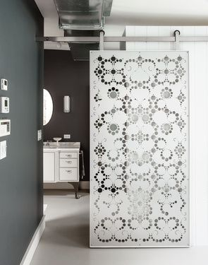 A budget friendly brownstone renovation in Brooklyn | Master Bath | The bedroom is configured as a casual open suite, with a sliding aluminum screen as the only barrier separating an adjacent bathroom and walk-in closet |  The screen's dappled, lacelike pattern was designed by Fiyel Levent, a local artist and architect