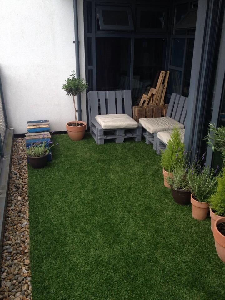 Artificial grass pallet chairs on balcony balcony