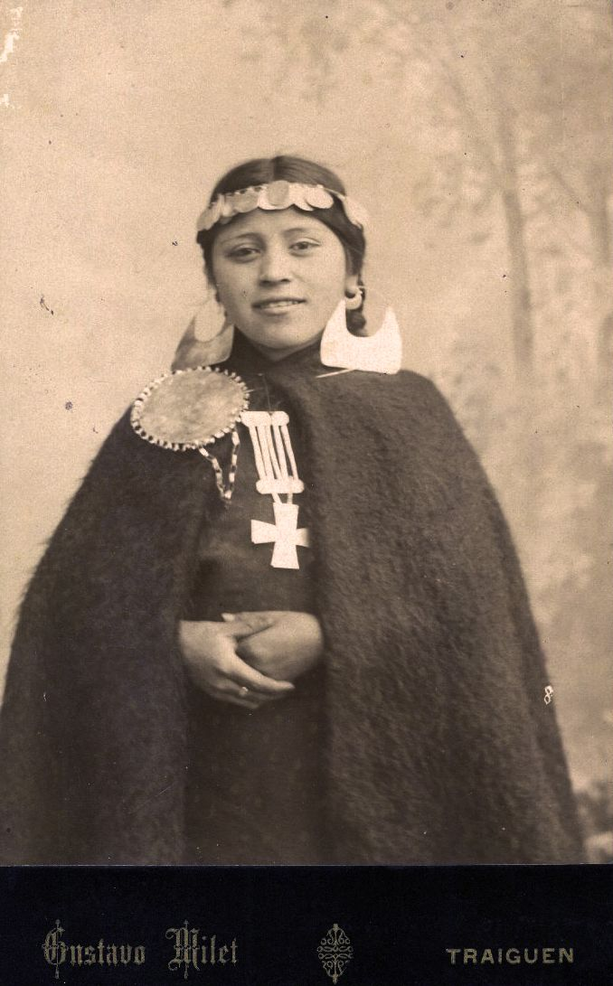 Chile | Studio portrait of a young Mapuche woman posed in front of a painted background of an outdoor scene; she wears a medella (coin-chain headdress), quipan (a square cloth, wrapped around the body), ikulla (shawl) or manta (blanket), chaway (earrings), tupu (clothes pin), trapelakucha (pectoral pendant) | ca. 1890. Traiguen, Araucania