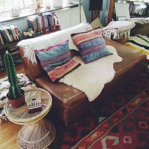 Brown leather couch, multicoloured/patternsed cushions, cream/fur throws, plants, pattern rug