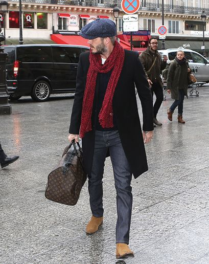 Shop this look on Lookastic:  http://lookastic.com/men/looks/flat-cap-scarf-crew-neck-t-shirt-cable-sweater-overcoat-jeans-chelsea-boots-holdall/5129  — Navy Herringbone Flat Cap  — Burgundy Scarf  — White Crew-neck T-shirt  — Navy Cable Sweater  — Black Overcoat  — Charcoal Jeans  — Tan Suede Chelsea Boots  — Dark Brown Print Leather Holdall
