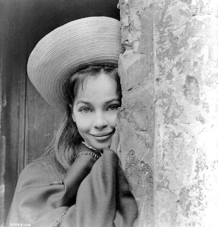Gigi(1958) Medium publicity shot of Leslie Caron as Gigi wearing hat next to wall.