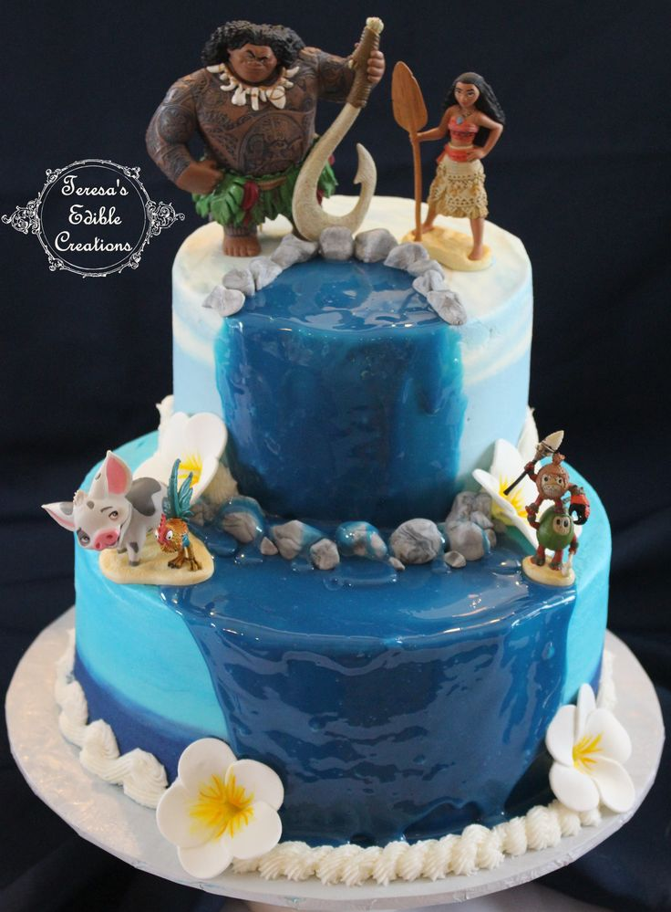 Moana cake Cake is covered in various blue tones of buttercream. Waterfall is made of dyed white chocolate mix. Topped with keepsake figurines.