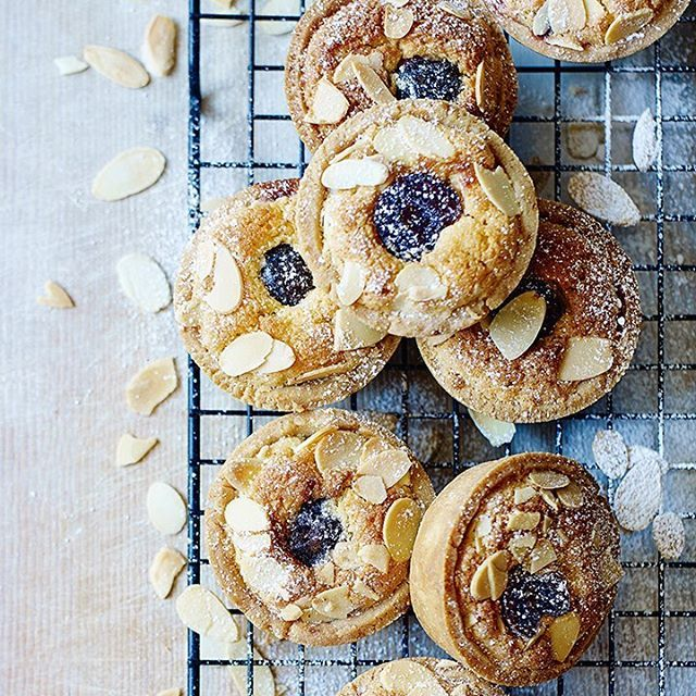 Sweet mini bakewell tarts topped with cherry jam and classic almond flakes. We've made the pastry with spelt flour for a delicious nutty taste.  Find the recipe in the link in our bio  #Bakewell #OnTheTable #homemade #Waitrose