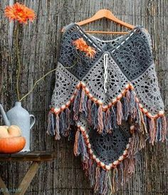 Granny square crochet poncho in lovely neutrals with a punch of color in the border / fringes
