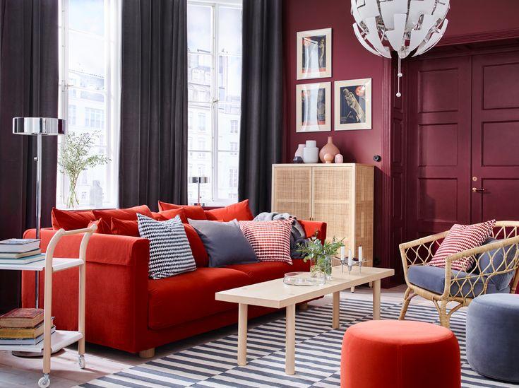 Sivá a tmavočervená obývacia izba s oranžovou pohovkou, pásikavým kobercom a ratanovým kreslom.
