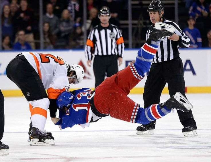 While referees look on as Philadelphia Flyers' Luke Schenn, left, throws New York Rangers' Daniel Carcillo