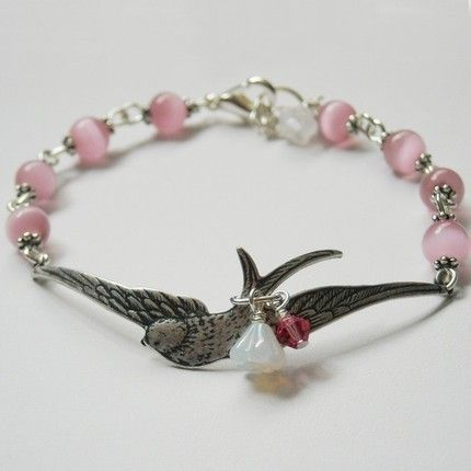 Get this charm bracelet !  Wings of Peace bracelet with pink pearls and sparrow -  adorned with a white glass lilly and a fuschia crystal !