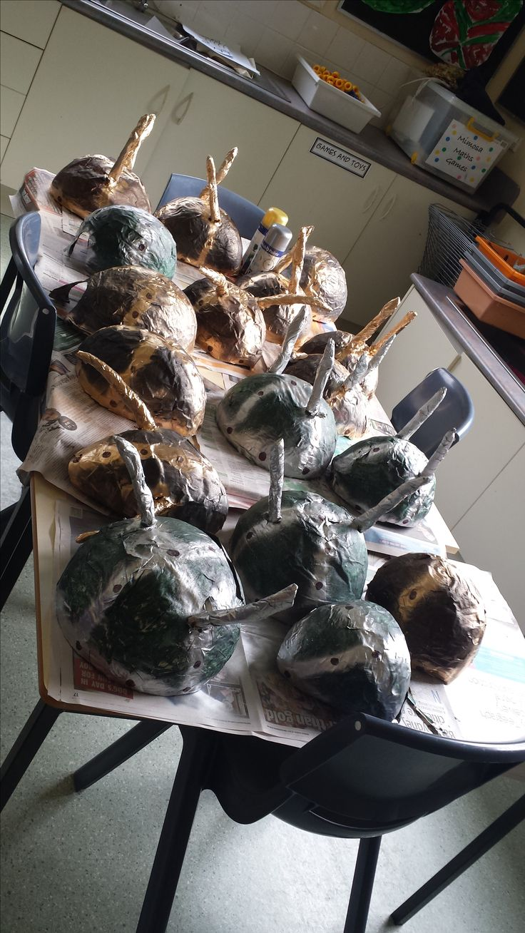 Viking helmets, made during a Vikings and Pirates unit.  The shape was created on the top of a balloon with paper mache (6-7 layers, the more the stronger). Eye rims and nose rims are cut out, then the whole dome was painted.  Once dry details are spray painted on around the rim and crossed over the top.  Bolts were drawn on with a marker.  Horns are rolled from news paper and taped with masking tape and fixed by cutting holes in the sides and securing with tape.  took 4 weeks.