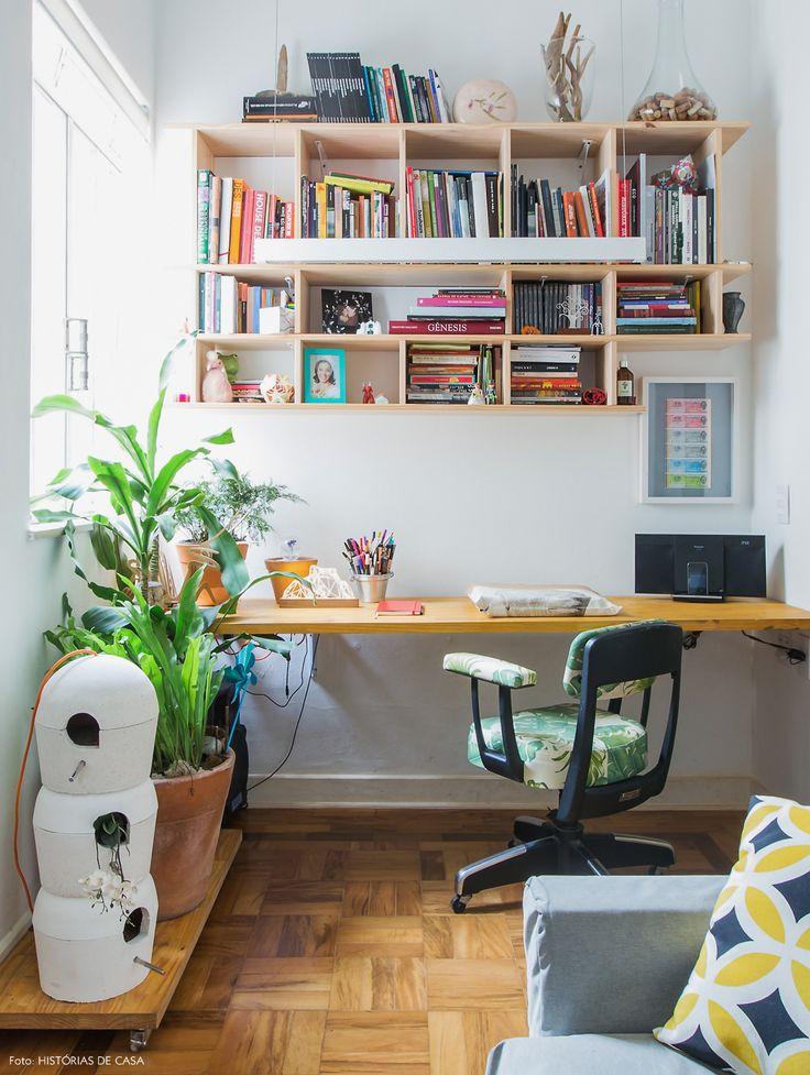 Home Office integrado ao estar tem bancada  e estantes feitas em madeira.