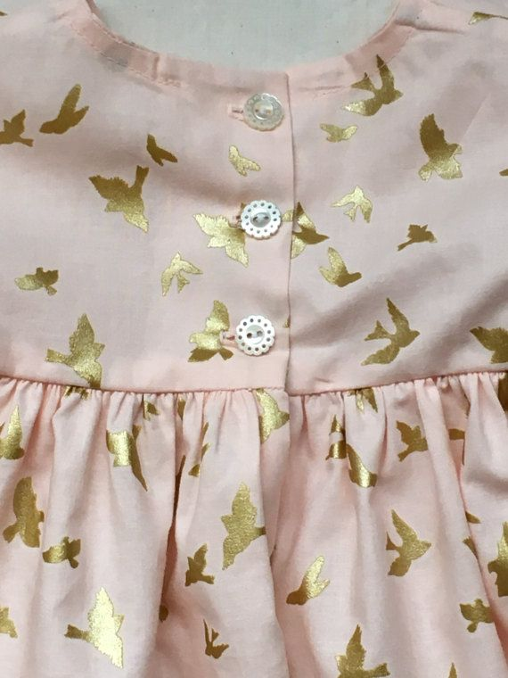 This little confection of a dress is handmade by me with the utmost attention to detail and in fabric and notions. Fabric is 100 percent premium cotton. Buttons are gorgeous real mother of pearl. The iridescent color looks beautiful against the blush pink. The birds are a really