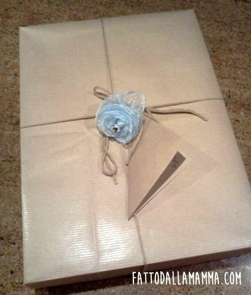 Scatola regalo riciclata con carta da pacchi e rosa in organza come decorazione.