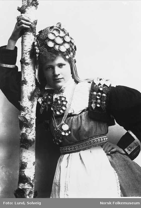 Digitalt Museum - Studiofotografi av kvinne med brudedrakt og brudehatt/krone på hodet. Stående lent mot bjørkestamme. Hofteutsnitt. Frontalt vendt. Ser ut av bildet.