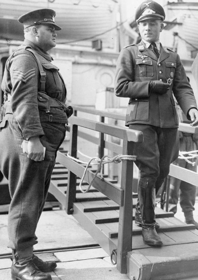 A German Luftwaffe officer POW disembarking in Newhaven, England glances contemptuously at a guard (ca. 1941)