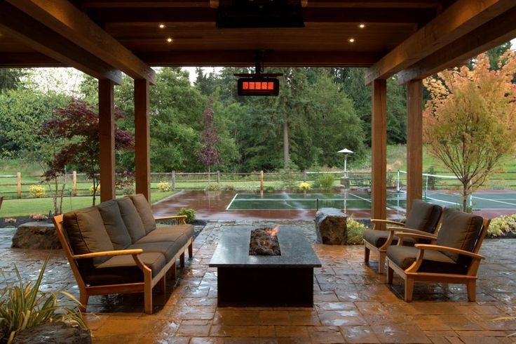 This transitional covered patio features comfy outdoor furniture situated around a rectangular fire pit, creating a cozy place in which friends and family can hang out and socialize. The patio offers the perfect vantage point for watching matches on the adjacent tennis court.
