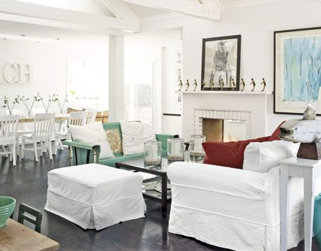 """Bright White Living Room Stock white paint and a flow-through floor plan. In the living room, bright white furnishings """"pop"""" against dark oak floors that have a patina from all the sand tracked in. Couch has denim slipcovers, which get washed every week."""