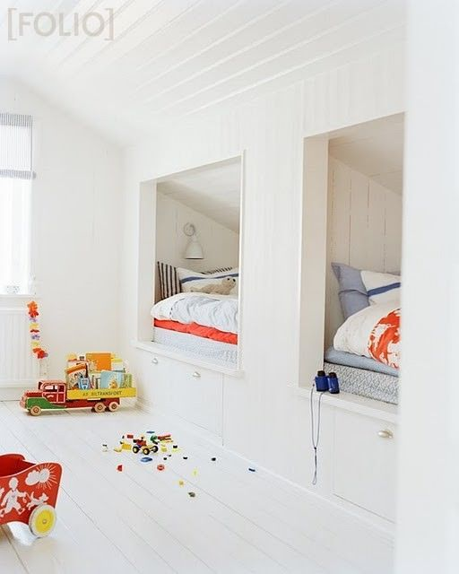 All-white wood and twin beds tucked under the eaves make great use of space in this children's shared bedroom.