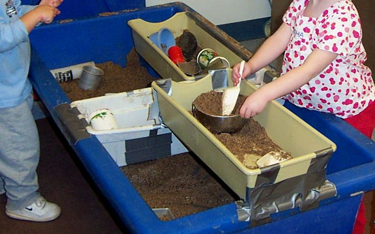 Three trays added to the table for sand play.  The white tray is a planter tray and spans the width of the table and is used to support the two tan trays.