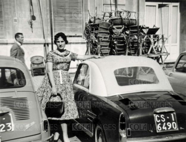 Una donna accanto ad una automobile FIAT Bianchina cabrio nera