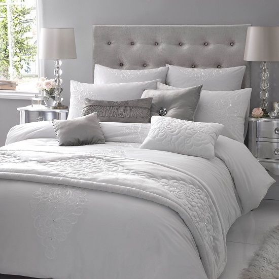 Bedding with lavish quilted satin throws, delicate cream pearls, and velvet cushions embellished with diamond encrusted brooches.