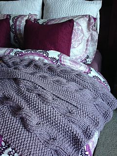 This knit afghan pattern uses a ribbed cable and moss/seed stitch, making it look the same from both sides. The pattern includes downsizing information. It is very easy and works up fast for an intermediate beginner knitter. The pattern creates a graceful scalloped edge. The length of the afghan is not specified in the pattern, but the yarn yardage is based on a 70-inch length.