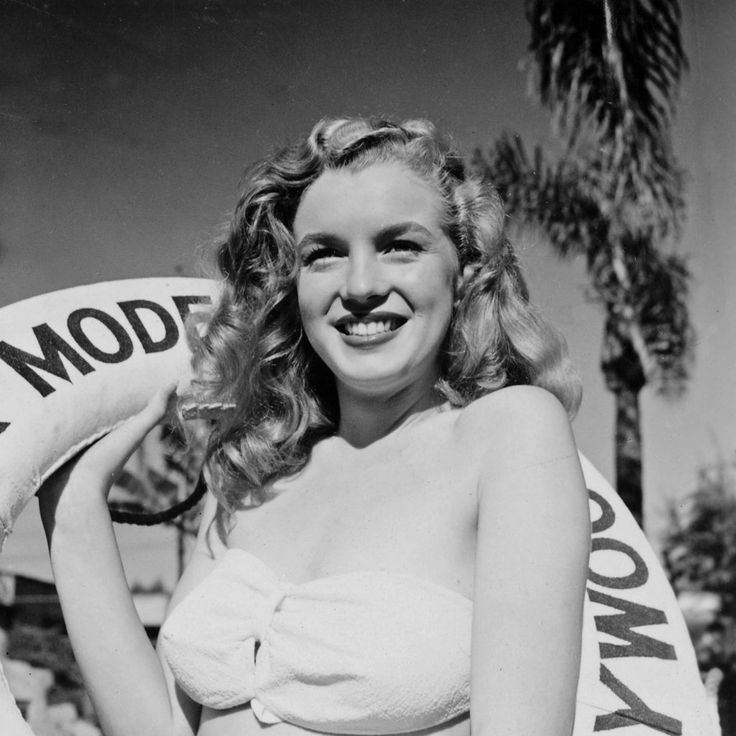Norma Jeane posing in the gardens of the Ambassador Hotel holding the Blue Book Models life ring.