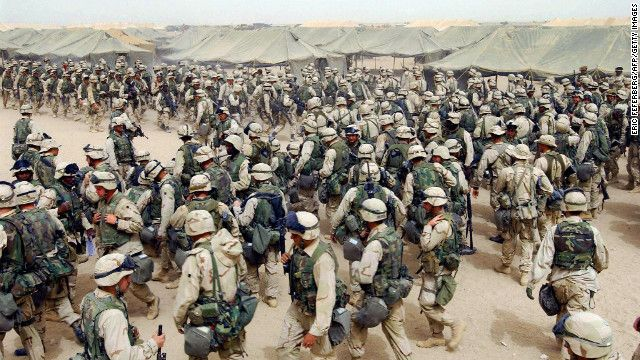 U.S. Marines in northern Kuwait gear up after receiving orders to cross the Iraqi border on March 20, 2003. It has been 10 years since the American-led invasion of Iraq that toppled the regime of Saddam Hussein to enlarge the profits of our own oil cartels.