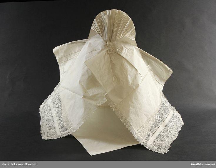 Stärkt klut i originalbindning med monterade klutband i bomull. Klutbanden har 2 rader med trädd tyllspets i traditionella sydskånska mönster inom ram av enkel utdragssöm. Banden kantade med uddspets i tyllträdning.