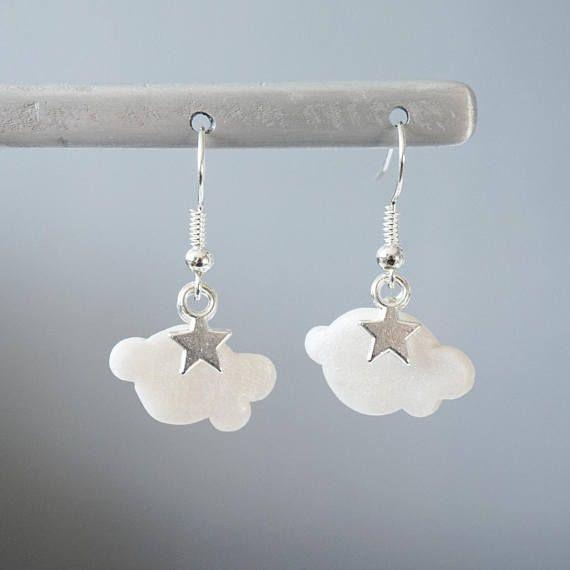 Boucles doreille Nuage blanc nacré et étoile Les boucles doreille sont constituées dun nuage en pâte polymère (fimo) de couleur blanc nacré ainsi que dune breloque étoile. Les attaches sont de couleur argentée, pour oreilles percées. Dimensions des nuages : 2cm x 1,3cm environ