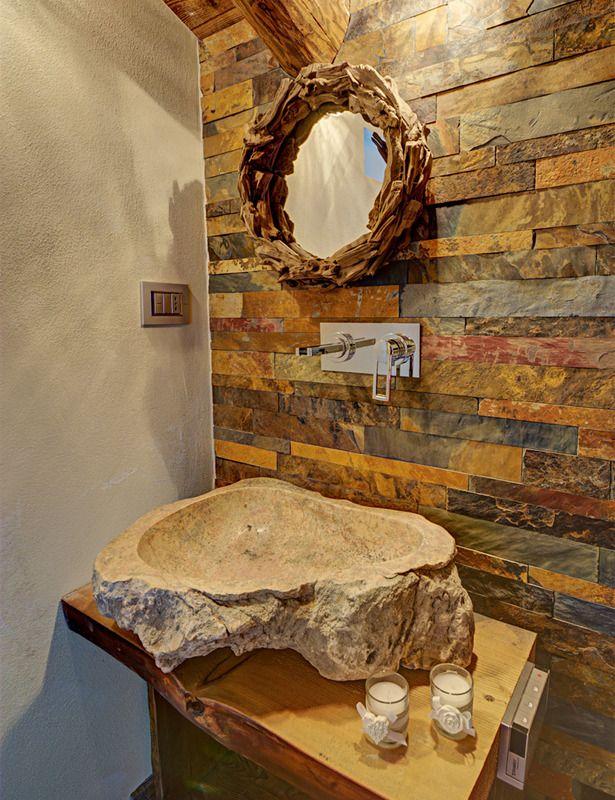 Un baño con lavabo de roca natural y pared de piedra.