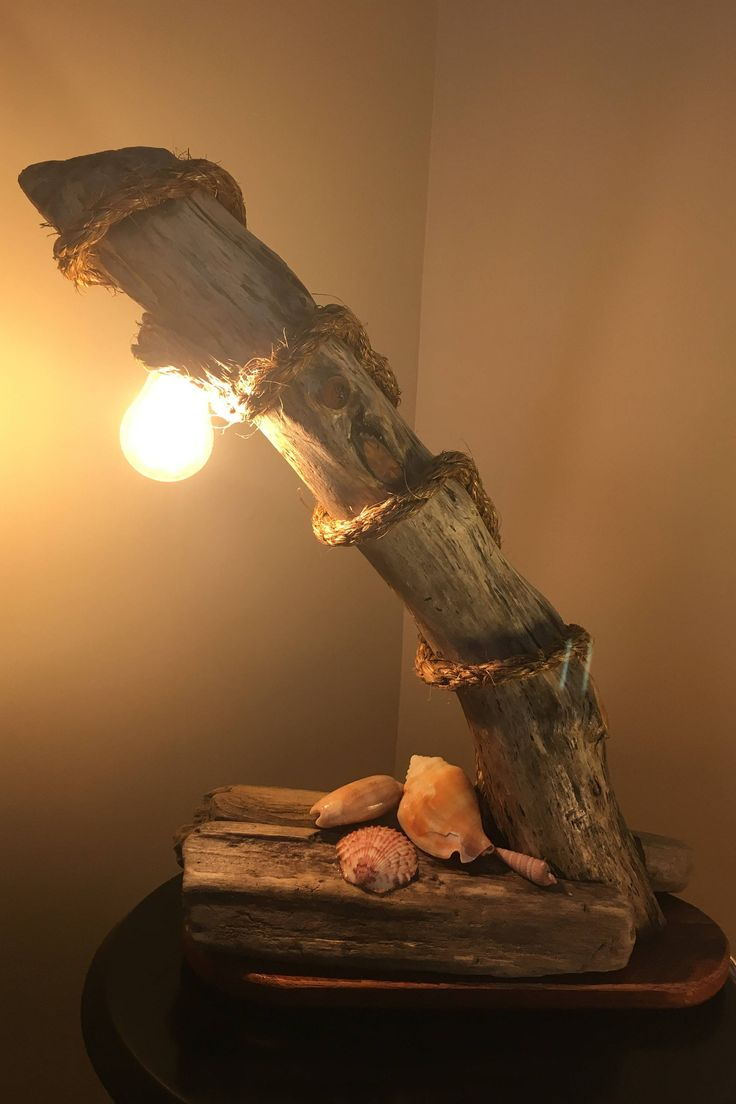 This is a nautical desk lamp made with beach drift wood, reclaimed wood base, natural shells and natural weaved rope. The lamp includes a stylish LED light and rocker switch. Bring the look and feel of the beach to your desk! Proudly made by Dark Horse Woodworking.