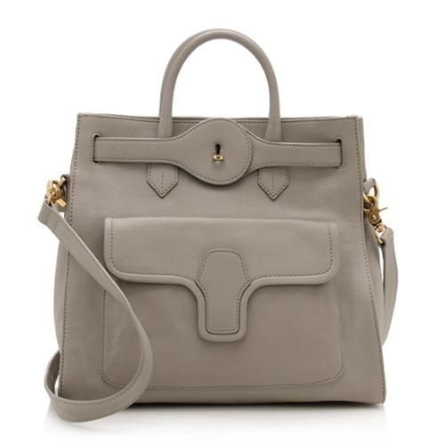 This Balenciaga tote is made from smooth grey calfskin with antique gold-tone hardware. Details include two rolled handles, a front pocket, belted detail, and turnlock closure. The interior is lined in light grey leather with one zippered pocket. Carry this style on the forearm or over the shoulder with a detachable strap.