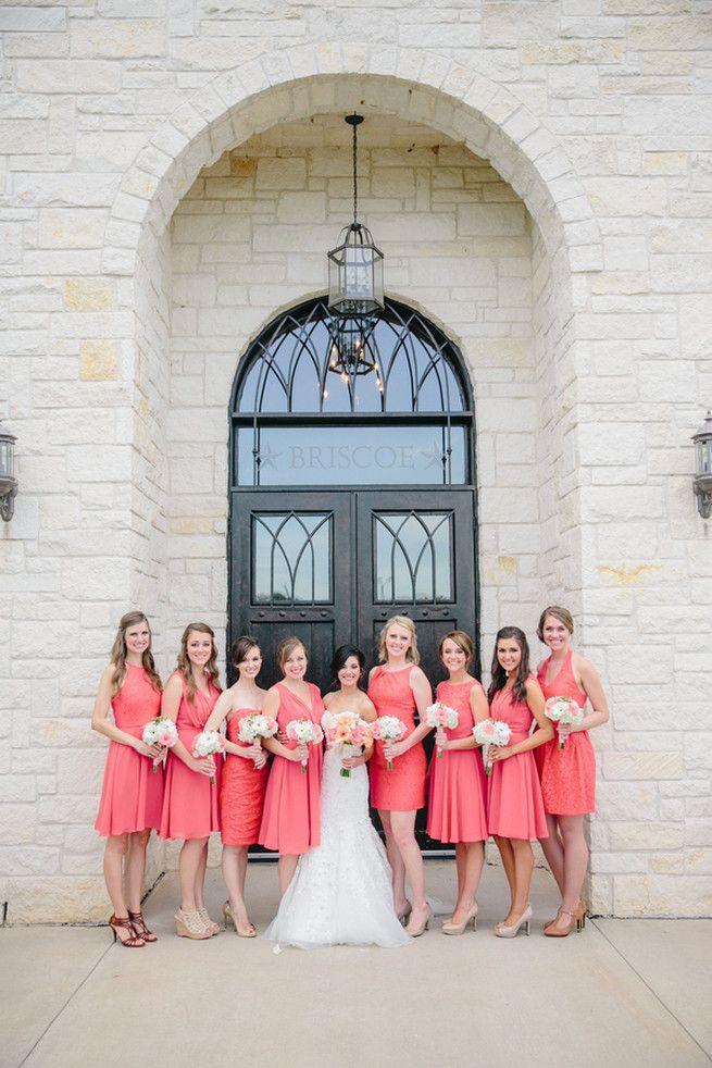 Coincidentes corto vestidos de dama de honor de coral con melocotón y ramos de dama de honor blancas.