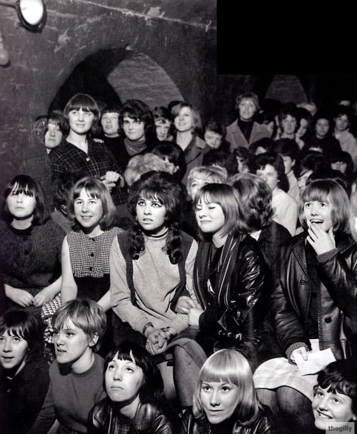 "Fans watching The Beatles at the Cavern Club, Liverpool, early 1960s. ""They'd keep their rollers in and jeans for the first groups. Then when it got near the time for the Beatles to come on, if there was a gang of four, say, they would go off in turns to the Ladies with their little cases to get changed and made up. When the Beatles came on they looked as if they'd just arrived.""  (Maureen Cox)"