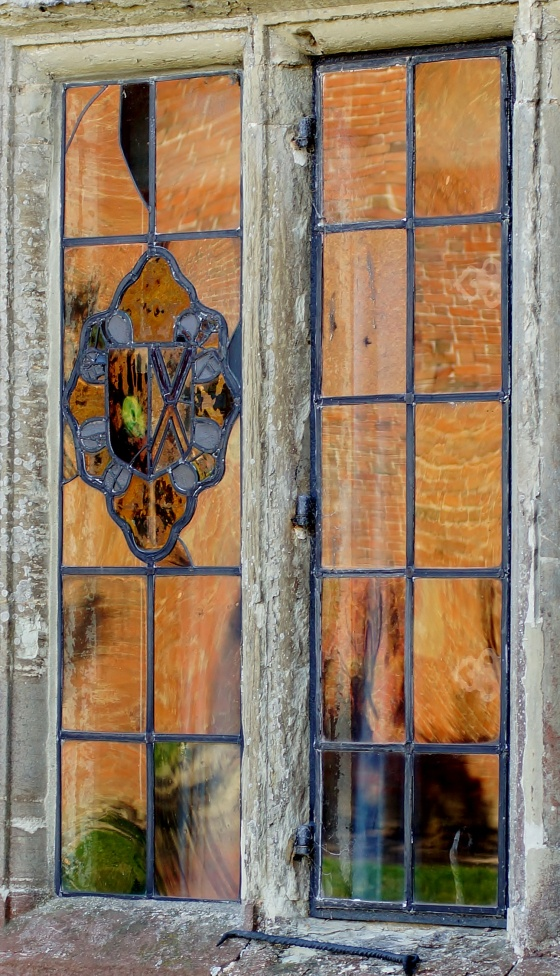 Sun drenched wall reflected in ancient window – Baddesley Clinton