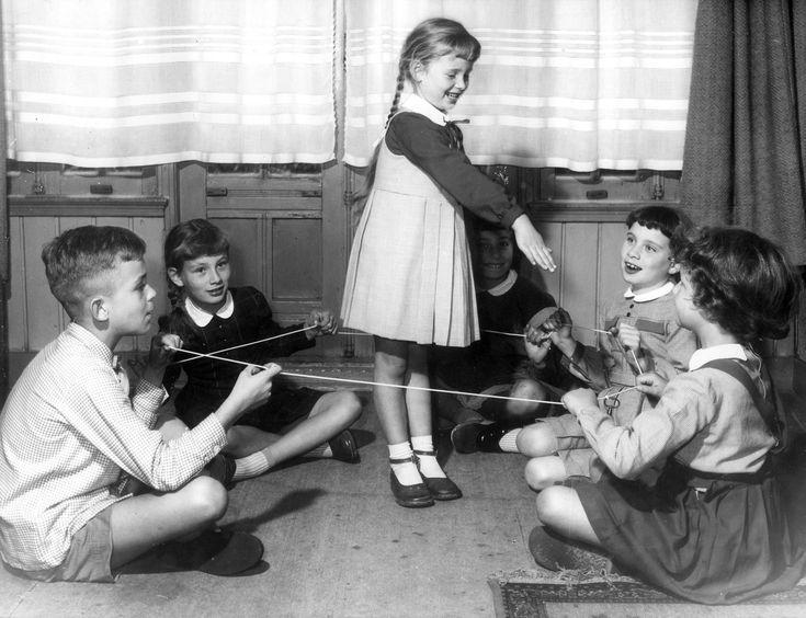 Kinderen spelen binnen een gezelschapsspel met een touw met een sleutel eraan, 1956.