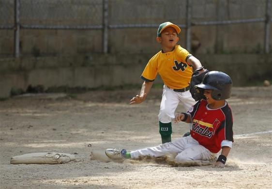 """A boy is put out at the third base during a baseball game at the """"23 de Enero"""" neighborhood in Caracas March 1, 2011.  REUTERS/Jorge Silva"""