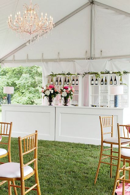 White wooden bar with crystal chandelier.  Coral flowers and natural wood chiavari chairs.  Tented wedding in Columbus Ohio designed by Bliss Wedding & Event Design.