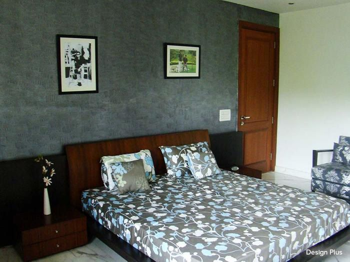 A textured gray wall with a classic brown door adds poise to this simple and neat bedroom #bedroom #homedecor #gray #contemporary Design Courtesy- Design Plus, Delhi