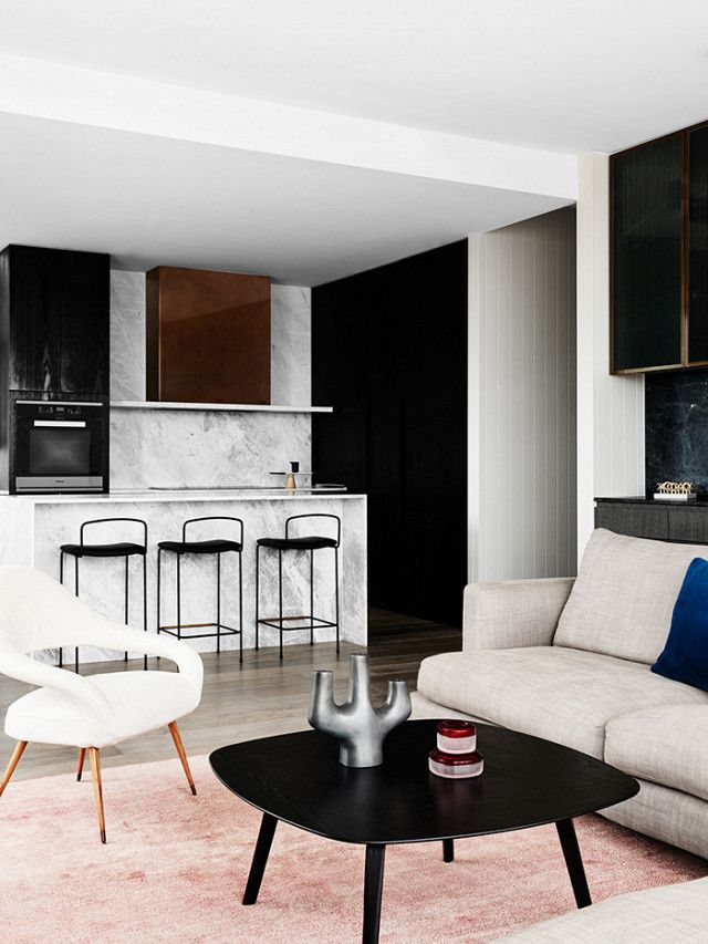 Minimalist living space with an open kitchen with a bronze plated stove hood, a blush rug, and a gray couch
